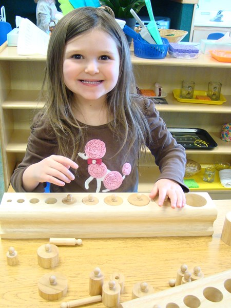 smiling montessori girl playing with manipulatives at Skipwith Academy